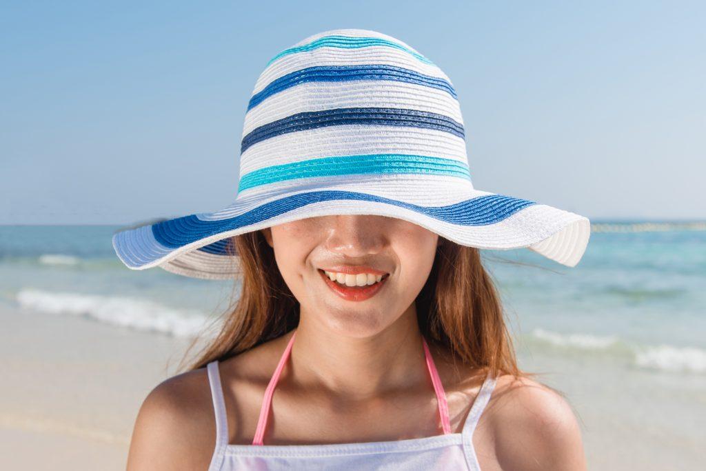 beach hat hair protect sun summer holidays vacation girl in bikini standing o